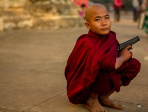 Boy Monk with Gun -  Photo and caption by Joyce Le - At the annual Ananda Harvest Festival in Bagan, Myanmar, thousands of monks from all over Myanmar came to receive alms. While walking around the vast temple grounds, I chanced upon this boy monk who was playing with his toy gun. Even though it was only a toy gun, I found this image a disturbing juxtaposition of the peace that Buddhism embodies and the violence that guns symbolise.Mesurier/National Geographic Traveler Photo Contest