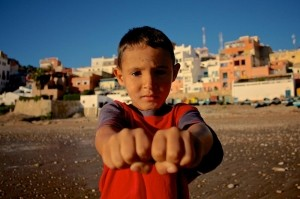 Left or right? -  Photo and caption by Thomas Pieters/National Geographic Traveler Photo Contest -  I was taking some shots on the beach of Taghazout, Morocco, when this little guy came up to me asking in what hand he was holding a coin. After playing along I asked if I could take his picture.