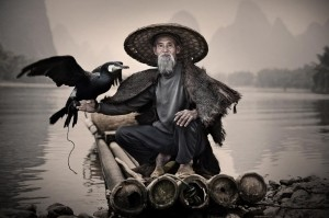 Mr. Huang Yue Chuang -  Photo and caption by Andrey Pavlov/National Geographic Traveler Photo Contest -  This photo was taken on the bank of Li-River close to Xingping fishing village. Mr. Huang and his four brothers are from the last fishermen that still keep the tradition of fishing using specially trained cormorants.  In recent days, this ancient technique has transformed into a tourist attraction and a source of income for Mr. Huang, who desperately needs funds for buying medicines for his sick wife.