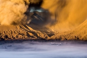 Temple At The Foot of Mount Bromo -  Photo and caption by Tim Jenka/National Geographic Traveler Photo Contest -  At the foot of the active Volcano Bromo on the Island of Java lies the Hindu Temple Pura Luhur Poten which is often immersed in a soft mist at dusk. On this day Mount Bromo showed unusually strong activity, which lead to a exceptionally high and dense dust cloud.
